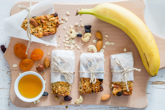 Granola bars and ingredients, white wood background
